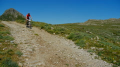 Pan of biker on mountain bike going down a gravel road Stock Footage