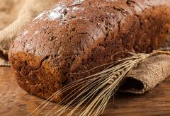 Brown bread and ears of wheat closeup Stock Photos