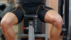 Young muscular man in the gym wearing training his hands, cam moves upwards Stock Footage