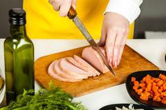 Cook knife cuts sausage Stock Photos