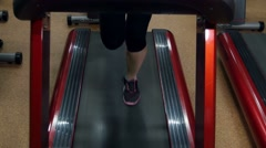 Athletic girl doing an exercise on running track in the gym, slow motion, cam Stock Footage
