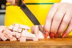 Woman cuts sausage cubes Stock Photos