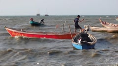 A young man tries to make a wooden motor boat, rocking on the strong waves, Asia Stock Footage