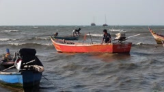 Retro longtail wooden boat rocks in a storm, fishermen preparing to go to sea. Stock Footage