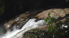 Fast flowing stream water passes over smooth rock Stock Footage