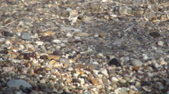 Closeup clear sea water waves  on a beach with small rocks. Summer holiday. Stock Footage