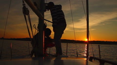 Dusk at sea, crew working on sailing yacht, coming home Stock Footage