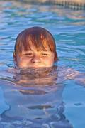 Child has fun in the outdoor pool Stock Photos