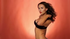 Brunette woman in sexual black bra in front of cam on vinous background, slow Stock Footage