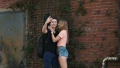 Hipster young couple on grunge city wall taking self portrait Stock Footage
