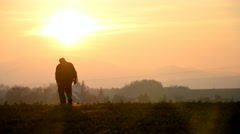 Old man walking across the field to the village at sunset Stock Footage