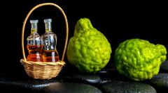 Aromatic spa concept of bergamot fruits and  bottles essential oil in basket  Stock Photos