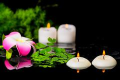 Stock Photo of spa background of plumeria flower, green branch Asparagus, fern and candles o