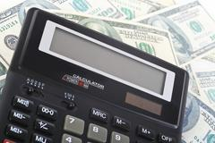 Calculator on banknotes Stock Photos