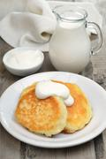 Fritters with sour cream and milk jug - stock photo