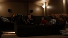 Kids watch a movie in a home theater room Stock Footage