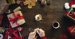 Top view Christmas hands writing name on gift card for presents at wooden desk - stock footage