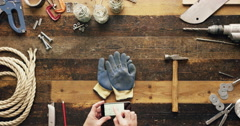 Top view artisan craftsman hands using smartphone touchscreen viewing building Stock Footage