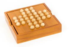 Peg solitaire wooden puzzle, isolated image - stock photo