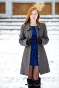 Portrait of young pretty redhead woman in blue dress and grey coat - stock photo