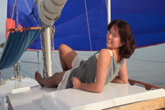 Pretty girl relaxing on yacht, smiling flirtatiously at camera - stock footage