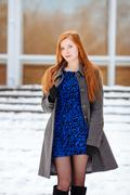 Portrait of young beautiful redhead woman in blue dress and grey coat - stock photo
