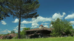 Time lapse with moving clouds over country house in old village Stock Footage