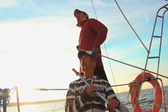 Young sailor and senior captain on sailboat, teamwork, help Stock Footage