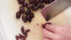 Black olive preparing - removing pit Stock Footage