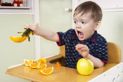 Small boy playing with his fruit - stock photo