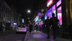 people walking on pavement at night and entering colorful shop - stock footage