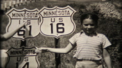 1717 - children next to highway 14, 16, 61 markers - vintage film home movie Stock Footage