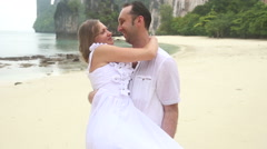 Groom carries blonde bride in arms and kisses Stock Footage