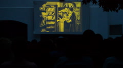 Projection of a old movie in a big screen with public Stock Footage