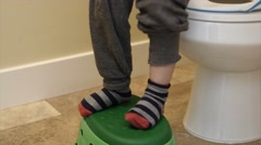 A little boy pulling up pants after going to the bathroom Stock Footage