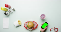 Top view man using smart phone at american diner fast food restaurant hands from Stock Footage