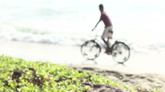 Indian guys ride bike along waves of sea Stock Footage