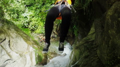 Tourist woman is sent by zip line over the waterfall while canyoning, action Stock Footage