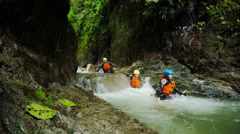 Canyoning trip in Ecuadorian rainforest, group of three tourists, static camera Stock Footage