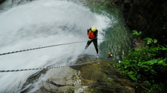 Real-time action shot of two tourist rappelling trough tall waterfall, static - stock footage
