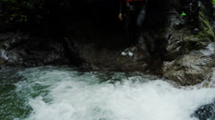 Active men jump into waterfall while canyoning intro Ecuadorian rainforest, low Stock Footage