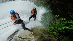 Real-time action shot of two tourist rappelling trough tall waterfall, static Stock Footage