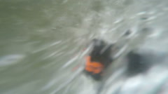 Whitewater tubing adventurer rescued by security kayaker, slow motion, camera Stock Footage