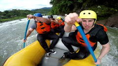 Oversized guy paddle hard on whitewater rafting boat, slow motion footage from Stock Footage