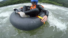 Unique POV of whitewater tubing enthusiast, camera rotates around the talent and - stock footage