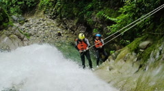 Adult tourist couple rappelling into large waterfall, fixed camera, shot from Stock Footage