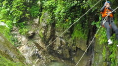 Young girl is sent by zip line over the waterfall while canyoning, action camera Stock Footage