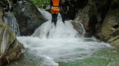 Canyoning trip, young women being dropped in waterfall by the tour lieder, Stock Footage