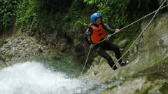 Adult women rappelling huge waterfall in Andes rainforest, static camera, shot Stock Footage