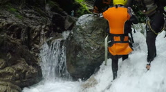 Canyoning trip, young boy being dropped in waterfall by the tour lieder, camera Stock Footage